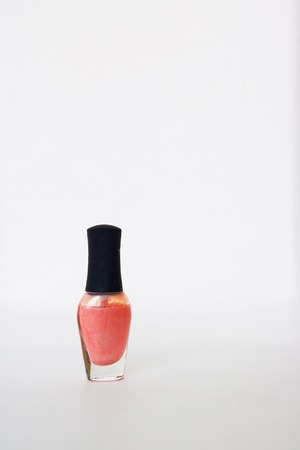 Glass bottle with black cap with pearl coral nail polish. Isolated object on white background. Nail polish. Beauty. Colour. Coral. Copy space, manicure