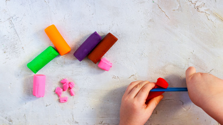 Colorful clay plasticine, modelling clay pieces with childs hands, horizontal, education, child psychology, neuropsychology fine motor skills manual dexterity copy space mental health