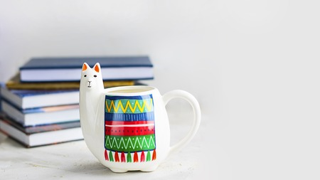 White Llama mug with pile of books on light grey empty background, horizontal with copy space for text or design. Trendy animal accessories for school and office