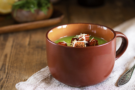 Green cream soup with red croutons and grated cheese in brown mug on natural ctoth on angle of old rustic wooden table, defocused ingredients Horizontal Healthy vegetarian food