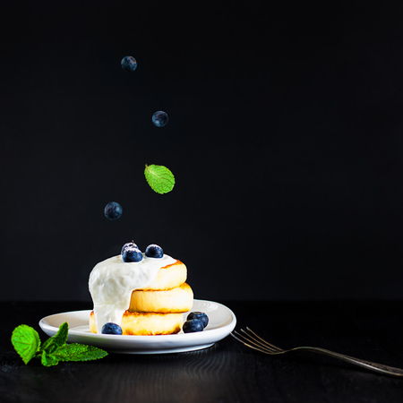 cottage cheese pancakes one on another topped with cream, blueberries and sugar powder on black background with fork and green mint leaves, breakfast, Square with copy space for text and design Banco de Imagens