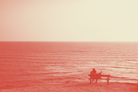 Couple lovers on bench look at blue sea. Sihlouette Coral duotone Stock Photo
