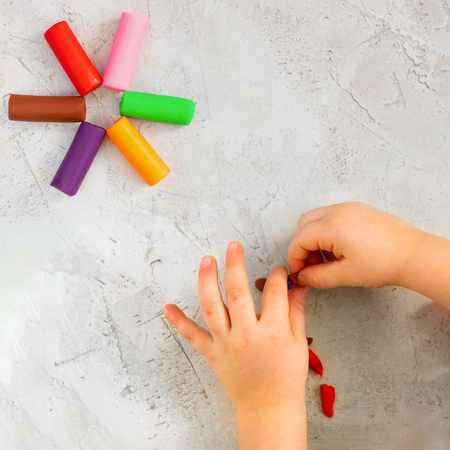Colorful clay plasticine, modelling clay placed like flower with childs hands, square, education, child psychology, neuropsychology fine motor skills manual dexterity copy space build mental health Stock fotó