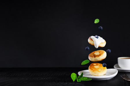 three cottage cheese pancakes topped with cream, blueberries, mint leaves fall down on white plate, defocused cup of coffee behind, black background, breakfast, Levitation Horizontal, copy space