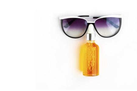 Bouteille orange d'huile d'écran solaire avec des lunettes de soleil bleu foncé placées comme un visage humain sur un fond blanc vide horizontal avec espace de copie. Appartement contemporain de vacances. concept de soins de la peau de l'homme.