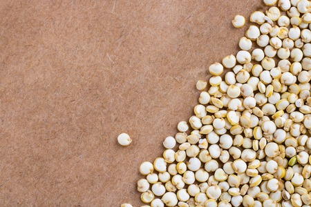 Seeds of uncooked Chenopodium quinoa, source of protein for vegetarians on brown natural paper background, Macro with copy space for text and design Banco de Imagens