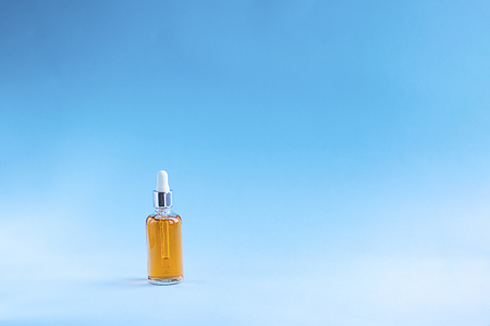 mockup orange plastic bottle with oil on blue background. Horizontal with copy space. Beauty and cosmetics concept about Slim body and Sun screen, health care skin, hair protection, UV filter. Stockfoto