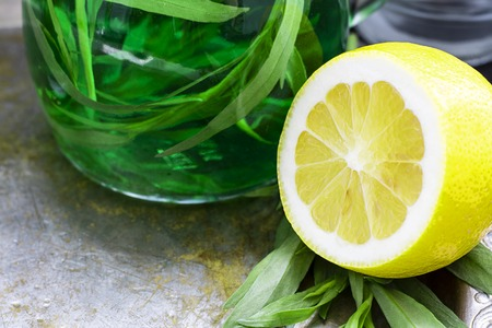 Half of fresh yellow lemon with defocused green drink with tarragon on background. Ingredient for Sparkling beverage, alcohol drink. Horizontal with copy space Banco de Imagens