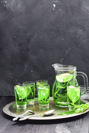Summer cold green drink with tarragon, mint and lemon in glass decanter and small shots with ice, one in focus in focus. Sparkling beverage, alcohol drink on dark background Vertical with copy space