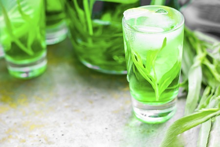 Summer cold green drink with tarragon, mint and lemon in small shot with ice and defocused decanter on background. Sparkling beverage, alcohol drink on dark background. Horizontal copy space
