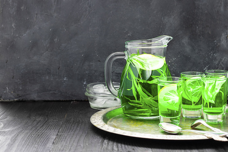 Summer cold green drink with tarragon, mint and lemon in glass decanter and small shots with ice, one in focus in focus. Sparkling beverage, alcohol drink on dark background Horizontal with copy space