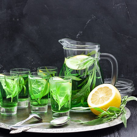 Summer cold green drink with tarragon, mint and lemon in glass decanter and small shots with ice, one in focus in focus. Sparkling beverage, alcohol drink on dark background. Square, copy space Banco de Imagens