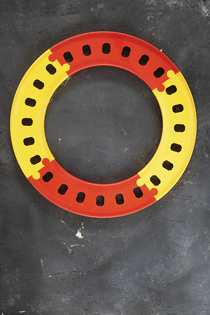 Plastic yellow and red round road on black chalkboard background with copy space. Top view. Creative concept for transport system, things for kid playing, education and schemes for business