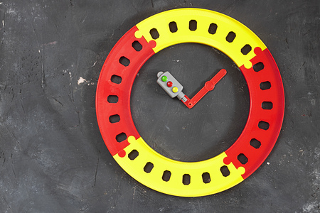 Plastic bright round road and toy traffic light as clock hands in the center on black chalkboard background with copy space. Top view. Concept for time management, schedule, timer and transport system