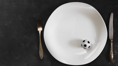 Small football ball on White plate with fork and knife on textured chalkboard background. Creative concept of diet and sport, special dietary plan for sportsmen. Horizontal with copy space. top view