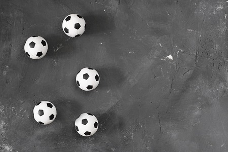 Many small football balls on black textured chalkboard background with copy space for text and design. Top view. Soccer. Sport.