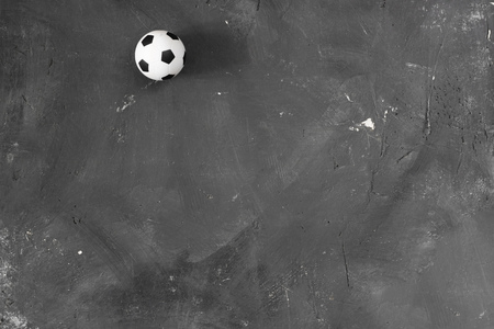 Small football ball on black textured chalkboard background with copy space for text and design. Top view. Soccer. Sport.