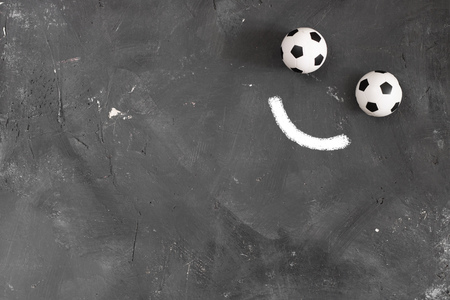 Smile made of Two small football balls and chalk line on dark textured blackboard background with copy space for text and design. Top view. Creative concept about sport, soccer and emotions. Banco de Imagens