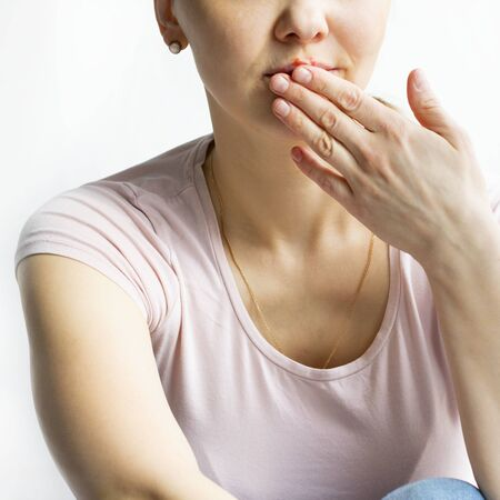 Red bubbles of virus herpes on lips of a woman in light pink t-shirt, lower part face is seen, which she tries to hide with her palm. Medicine, treatment. Square. White background