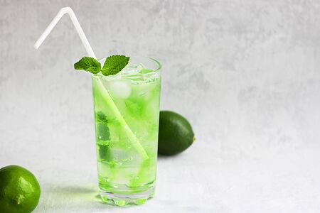 Summer cold green drink with lime, mint and lemon in tall glass with ice and straw and defocused fruit around on grey background. Sparkling beverage, alcohol drink, mojito coctail. Horizontal Stockfoto