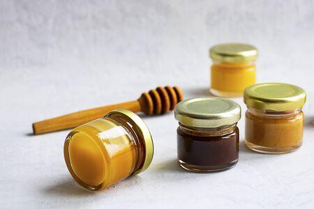 Vier kleine glazen pot met metalen dop met verschillende soorten en kleuren honing in lijn en houten lepel isoleren en op grijze cementachtergrond Gezond product, natuurlijk. Horizontaal
