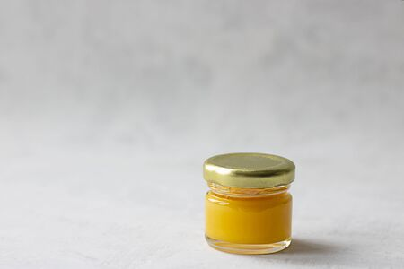 Small glass jar with metal cap with light yellow honey isolate on grey cement background with copy space. Healthy product, natural, Horizontal