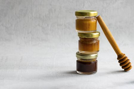 three Small glass jar with metal cap with different kinds and colours of honey one on another and spoon isolate and on grey cement background with copy space. Healthy product, natural. Horizontal Stock fotó