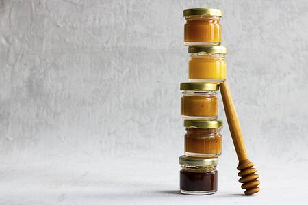 Five Small glass jar with metal cap with different kinds and colours of honey one on another and spoon isolate and on grey cement background with copy space. Healthy product, natural. Horizontal Stock fotó