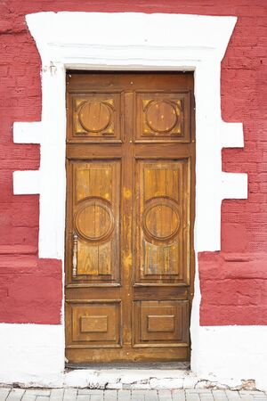 Beautifull door on the background of red painted textured brick wall. Russian style. Wooden architecture. Hand made carving, pattern Vertical Stockfoto