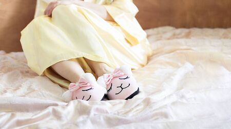 female feet wearing cute llama trendy pink slippers, lay on bed with wooden headboard and on pastel silk gown. Home Rest Relax Holidays Horizontal with copy space