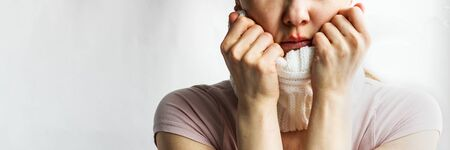 Lower part part of woman face with Red bubbles of virus herpes on her lips she tries to hide it under white knitted neckwarmer, Zoster, Cold, Medicine, Treatment. Horizontal copy space, winter disease