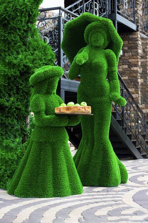 Green sculptures of young girl and a lady with umprella in long dress made from artificial grass. Girl holds wooden tray with fresh apples. Urban design, city architecture, park decoration. Vertical.