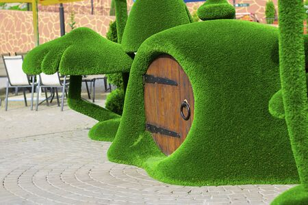Green sculpture of small house with round wooden door surrounded by mushrooms made from artificial grass.Vertical with copy space. Urban design, city architecture, park decoration