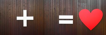 plus, equal and heart symbol on brown wooden wall. Long horizontal banner with copy space. Creative concept or wedding and St. Valentimes day