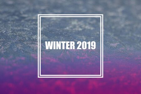 Ice patterns on glass of window with double frame and words WINTER 2019 Light violet and blue duotone. Horizontal banner. Selective focus. Creative background about frost, cold, christmas time.