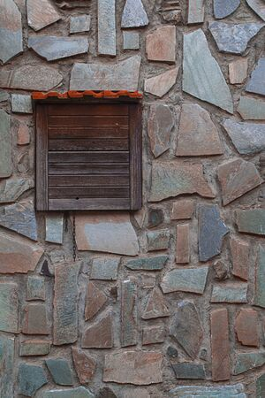 Stone wall exterior with small window closed with old wooden door, background with good texture. Vertical. For text and creative design Imagens