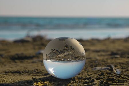 Glass ball in focus on the beach send near the sea with upsidedown reflection and lighs flecks on the defocused background. Horizontal with copy space