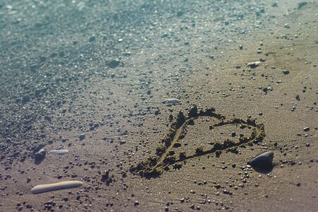 Heart on the sand beach. Conceptual design about relations, love and travelling, romantic holiday, honey moon. Pink and blue duotone. St.Valentines day on sea. Horizontal with copy space