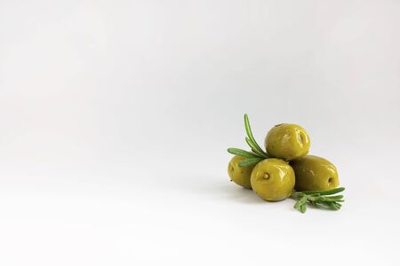 set of green marinated with herbs olives with fresh rosemary leaves on white background, horizontal with copy space. Isolate. Appetizer.