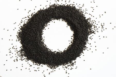 Dry sweet basil seed. Handful on white empty background circle shape. Healthy and super food. Horizontal. Isolate. Imagens