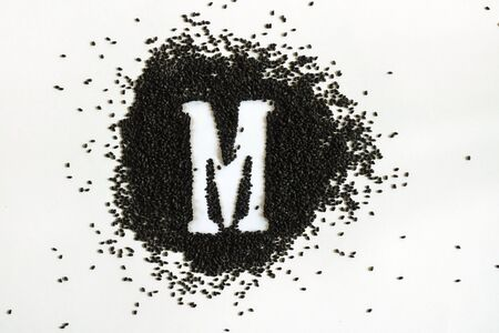Handful of sweet basil black seeds, letter M uppercase of English alphabet on white background. Black and white. Lettering. Typography. Horizontal. Healthy and super food. 스톡 콘텐츠