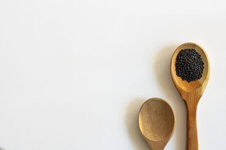 Sweet basil seeds in a wooden spoon and empty one near on white background. Horizontal with copy space for text and design about superfood and health, Isolate