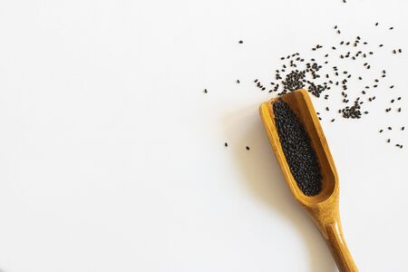 Sweet basil seeds in a wooden scoop on white background. Horizontal with copy space for text and design about superfood and health, Isolate Stok Fotoğraf