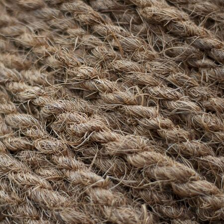 Rough Cord made from natural plant fiber. Rope detail, closeup. Wallpaper and background about fabtic manufacture, eco friendly material. Square. Brown tone. Copy space.