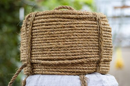 Big flat hasp of Rough Cord made from natural plant flax fiber. Rope detail, closeup. Wallpaper and background about fabtic manufacture, eco friendly material. Horizontal.