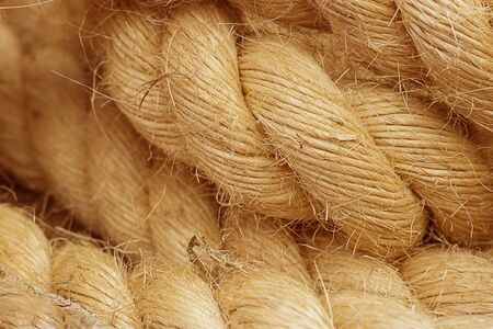 Rough Cord made from natural plant fiber. Rope detail, closeup. Wallpaper and background about fabtic manufacture, eco friendly material. Horizontal. Orange tone. Copy space.