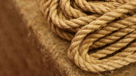 Rough Cord made from natural plant fiber. Rope detail, closeup. Wallpaper and background about fabtic manufacture, eco friendly material. Horizontal. Copy space. Brown tone. Selective focus. Banner
