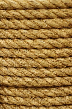 Rough Cord made from natural plant fiber. Rope detail, closeup. Wallpaper and background about fabtic manufacture, eco friendly material. Vertical. Copy space. Brown tone. Selective focus Imagens