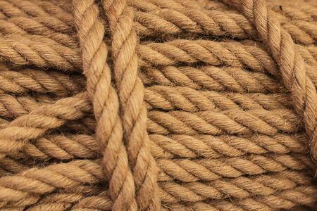 Rough Cord made from natural plant fiber. Rope detail, closeup. Wallpaper and background about fabtic manufacture, eco friendly material. Horizontal. Copy space. Brown tone. Selective focus Imagens