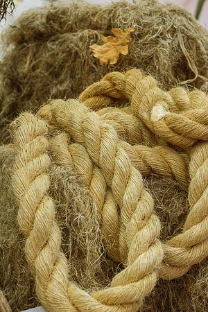 Szorstki sznur wykonany z naturalnego włókna roślinnego. Szczegóły liny, zbliżenie. Tapeta i tło o produkcji tkanin, materiał przyjazny dla środowiska. Poziomy. Vintage ton. Skopiuj miejsce.